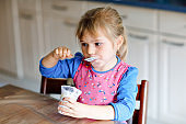 Little toddler girl eating yogurt for breakfast. Cute healthy baby sitting in the kitchen or at nursery and having meal.
