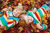 Two little twin kids boys lying in autumn leaves in colorful fashion clothing. Happy siblings having fun in autumn park on warm day. Healthy children with blond hairs and blue eyes with maple foliage.