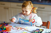 adorable baby girl learning painting with water colors. Little toddler child drawing at home, during pandemic coronavirus quarantine. Happy creative child, homeschooling and home daycare with parents