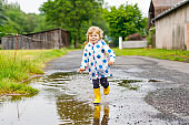 Little toddler girl wearing yellow rain boots, running and walking during sleet on rainy cloudy day. Cute happy child in colorful clothes jumping into puddle, splashing with water, outdoor activity
