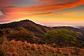 Foothills of Monteverde Cloud Forest Reserve, Costa Rica. Tropic mountains after sunset. Hills with beautiful orange sky with cloud. Evening landscape from Costa Rica. Mountain landscape from tropic