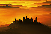 Scenic view of typical Tuscany landscape, house with hills during orange sunset, Italy
