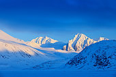 Evening mountain. White snowy mountain peak, blue glacier Svalbard, Norway. Ice in ocean. Iceberg in North pole. Beautiful landscape. Snowy hill with dark blue sky. Travelling in Arctic Norway.