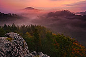 Cold misty foggy morning with twilight sunrise in a fall valley of Bohemian Switzerland park. Hills with fog, landscape of Czech Republic, beautiful national park Ceske Svycarsko. Beautiful landscape.