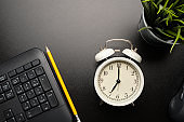 Vintage alarm clock in white color on black table that surround with black keyboard, mouse, yellow pencil and tree.