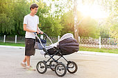 young man, father, walking with a stroller on the street, the concept of fatherhood, child care