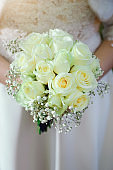 A bride in a white wedding dress is holding a bouquet of white roses. Close-up.