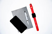 Gray notebook for writing on black background. Ballpoint pen. Smart watch with a red strap. Flat Lai, copies of the paste. View from different sides. Smartphone. Businessmen set kit white background.