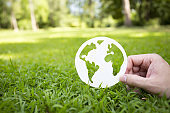 Close up hand holding earth paper. Save environment, world peace, earth day concept, paper globe on the grass with hands, blur