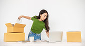 Startup small business entrepreneur SME, asian woman packing product into box. Portrait young Asian small business owner home office, online sell marketing delivery, SME e-commerce telemarketing concept
