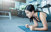 Gym asian crossfit woman working out doing push ups. Young mixed race fitness model training in fitness center. Sport and healthcare concept