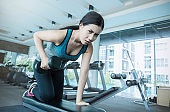 Sport asian woman hold dumbbell and training hard in the gym. Portrait of young beautiful girl warm up in sport club. Health care and medical concept