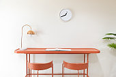 front view of orange study desk or workplace with metal electrical table lamp and white minimalist clock without number hanging on the wall