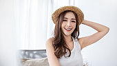 Portrait of young beautiful asian woman on holiday vacation summer time in white bedroom. Happy cheerful girl in summer. Korean makeup skincare. University woman fashion lifestyle concept.