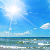 Seascape and sun on blue sky background.