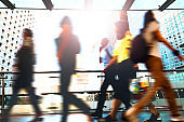 Blurred motion unrecognizable people walking at shopping mall footbridge in Central District Hong Kong