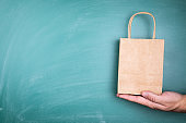 Paper shopping bag in hand. Copy space. Green chalk board background