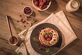Pancakes with raspberries, banana slices, pomegranate seeds and honey