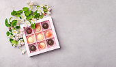 Chocolate candies in a festive box on a gray background. Holiday concept