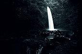 Dark View Of Nungnung Waterfall Splashing in Bali Jungle, Indonesia