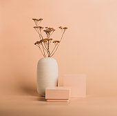 Modern abstract podium of geometric shapes dried flowers on pastel background