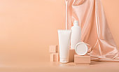 Cosmetic vials tube bottles white on modern abstract podium on pastel background
