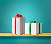 White gift boxes with a red and green satin ribbon on wooden shelf.