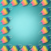 Frame of rainbow protective face masks in a row on light blue background.