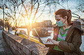 Woman using laptop with protective facial mask outdoors