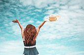 Happy asian women with holding hat stand to receive the wind and enjoy life on the beach vacation. beach, summer, liftstyle, positive mood, travel, relax concept.