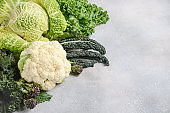 Different kinds of fresh organic cabbage on a gray concrete background.