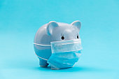 Piggy bank wearing a protective face mask