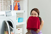 Asian housewife is laundry with washing machine.