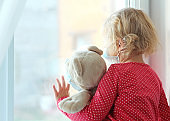 Toddler child in protective face mask sitting at window sill,caucasian kid portrait stay at home quarantine.Coronavirus,covid-19 pandemia prevention.