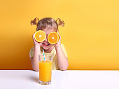 Child girl with oranges on eyes sitting at empty space table with glass of orange juice.Healthy vitamin child's nutrition.Kid with fruits.