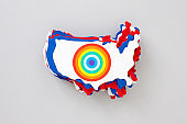 Stacked paper USA Maps with rainbow circle over them