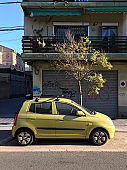 Green compact car parked in the street