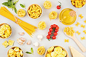 Flat lay with different types of traditional italian pasta. Penne, tagliatelle, fusilli, farfalle, spaghetti and cooking ingredients. Traditional italian cusine concept