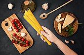 Flat lay of Ingredients for cooking italian pasta. Spaghetti, tomatoes, oil, garlic, parmezan. Top view of traditional italian cusine idea