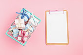 Christmas gift boxes in shopping basket and clipboard on pink background