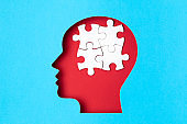 Papercut head with jigsaw puzzle pieces inside. Mental health problems, psychology, memory, logic, thinking process, solution, mental illness