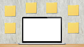 White blank screen laptop on the wood table with yellow blank sticky notes on wall background