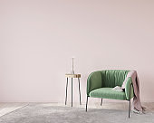 Soft green armchair on a pink wall background