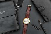 Man's wrist watch with handbag and purse on black.