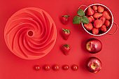 Top veiw of fresh and juicy sunmmer fruits and kitchen utensils on red background. Summertime, red fruits, vitamins, cooking, organic berries concept. Flat lay