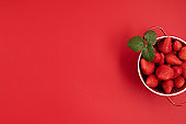 Top veiw of fresh and juicy strawberry on red background. Summertime, red fruits, vitamins, buy local, organic berries concept
