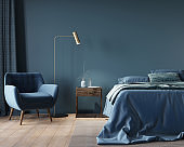 bedroom in dark blue with a wide bed, a wooden nightstand and a golden floor lamp
