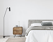 Bright bedroom with a wooden bedside table and a stylish floor lamp