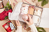 Preparing care package, sasonal gift box with marshmallow, tea,coffee or cacao box and christmas ornament