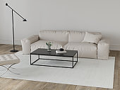 Living room in beige tones with leather sofa, metal table, pouf and floor lamp
